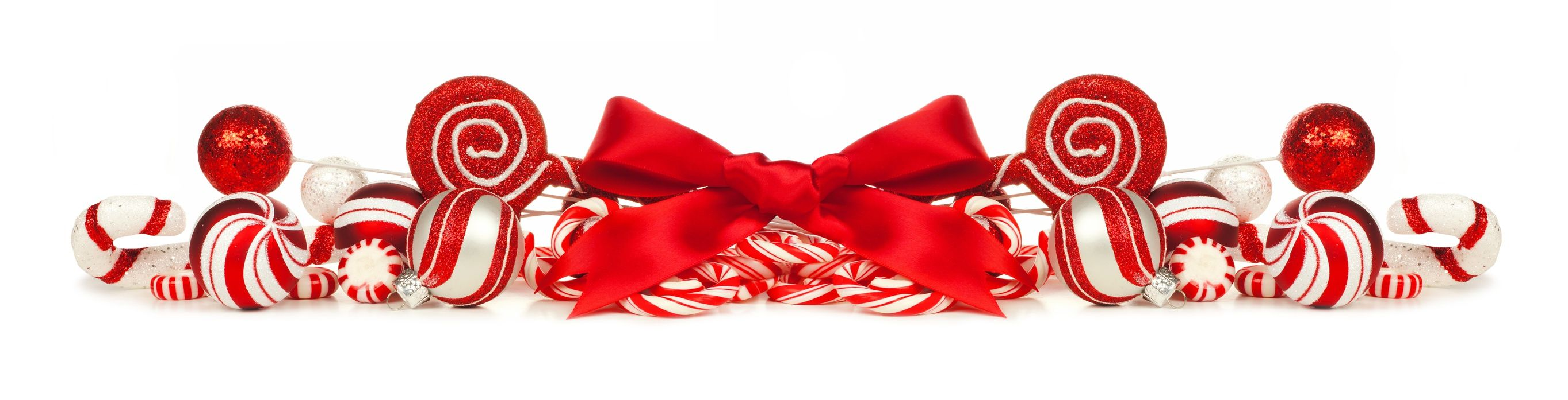 Christmas border of red and white baubles, bows and candy canes isolated on a white background
